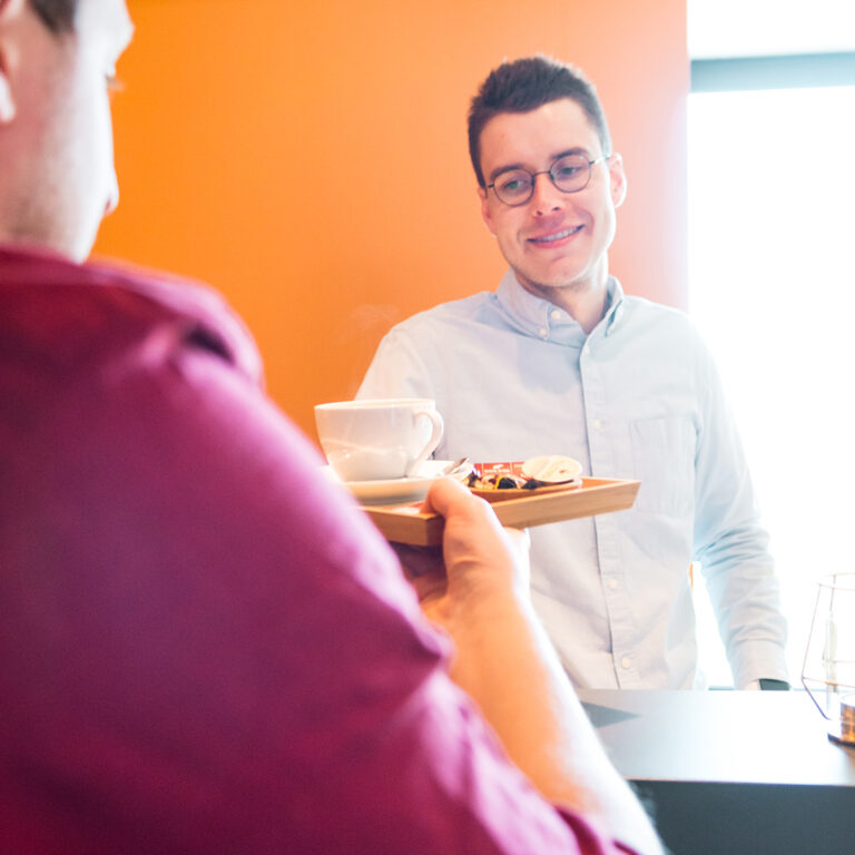 persoon geeft koffie aan andere persoon