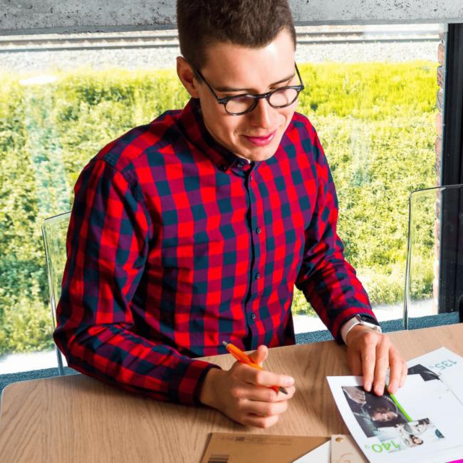 persoon bekijkt documenten aan bureau